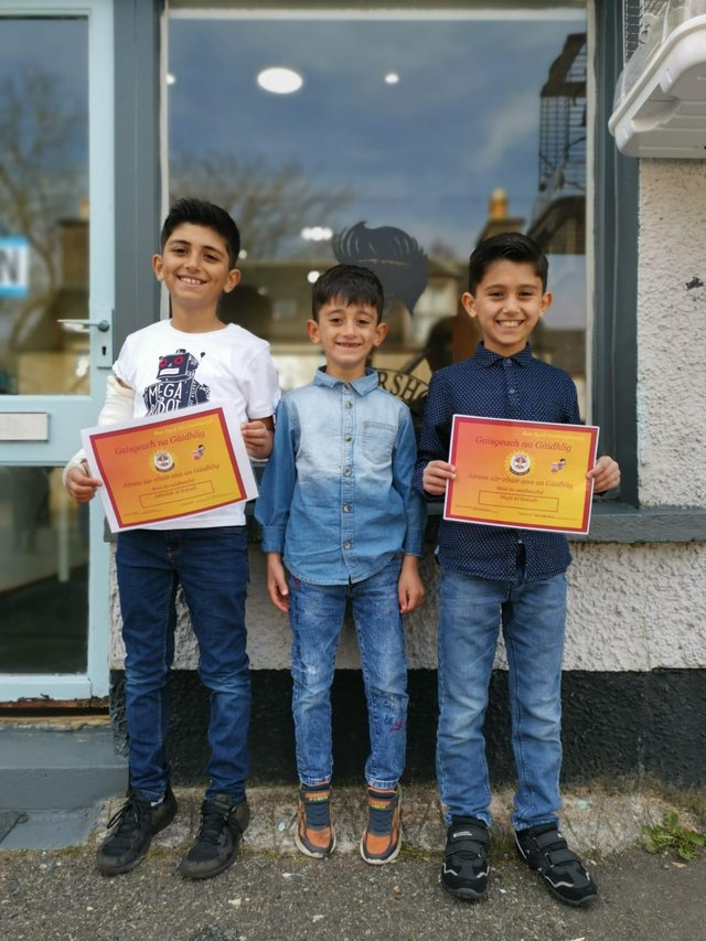 The three brothers Abdullah, Anas and Majd. Abdullah and Majd holding their Gaelic Certificates.